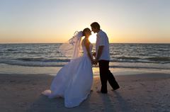 Bride & groom married couple kissing sunset beach wedding Stock Photos