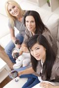 interracial group three women friends drinking wine together at home - stock photo