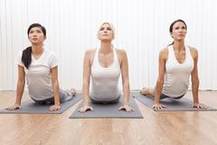 interracial group of three beautiful women in yoga position - stock photo