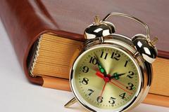 Golden alarm clock on the book Stock Photos