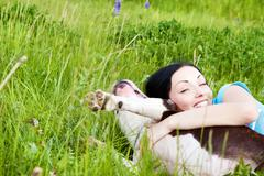 woman with dog playing in the grass - stock photo