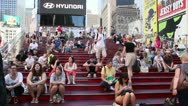 Stock Video Footage of People sitting on the red stepped seating in Times Square