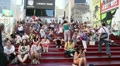 People sitting on the red stepped seating in Times Square Footage