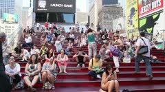 People sitting on the red stepped seating in Times Square Stock Footage