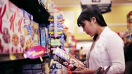 Stock Video Footage of Young Asian Woman Shopping for Sugary Cereal, Reading Label