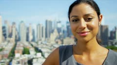 Portrait of Hispanic businesswoman on rooftop overlooking Manhattan   - stock footage