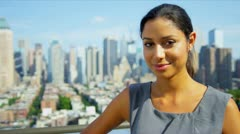 Portrait of Hispanic female business manager on rooftop overlooking Manhattan  - stock footage