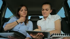 Young businesswomen working with two tablets on the back seats of car - stock footage