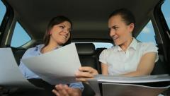 Two young businesswoman viewing documents in the back seats of car - stock footage