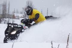 Quad bike's driver rides over snow track Stock Photos