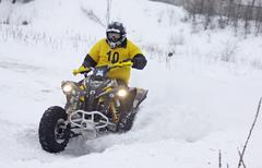 The quad bike's driver rides over snow track - stock photo