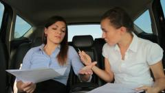 Businesswomen row in the back seats of car - stock footage