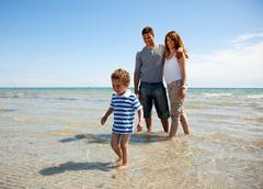 family enjoying the weekend on a sunny beach - stock photo