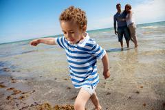 Young family on a tropical beach Stock Photos