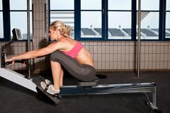Woman on indoor rowing machine Stock Photos