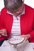 Pensioner does embroidery Stock Photos