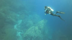 Scuba diver swimming high above deep coral reef Stock Footage