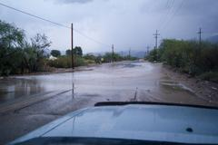 A flooded desert road right after a powerful monsoon storm - flash flood danger Stock Photos