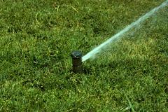 sprinkler spraying water - stock photo