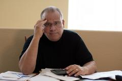 mature male worried and depressed about bills - stock photo
