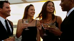 Multi ethnic friends drinking cocktails dressed in black at sunset party   - stock footage