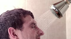 Man in shower with water on face Stock Footage