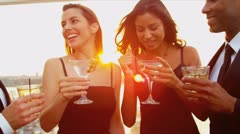 Multi ethnic women and men laughing and drinking at cocktail roof party   Stock Footage