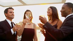 Multi ethnic girls drinking  with men at sunset outdoor party   - stock footage