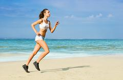 Stock Photo of young woman running alone on the beach