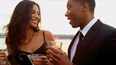Hispanic woman and African American man having fun at city cocktail party   Stock Footage