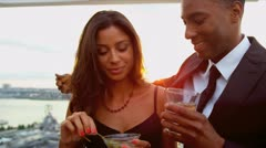 Diverse couple talking drinking at city cocktail roof party   Stock Footage