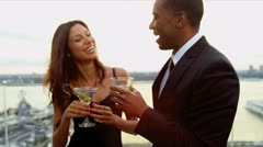 Multi ethnic couple taking and drinking at cocktail party dressed in black   Stock Footage