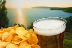 Glass of beer and potato chips in a landscape Stock Photos