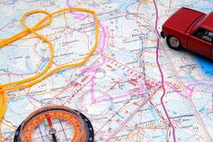 fragment of a map with a compass and model of the automobile - stock photo