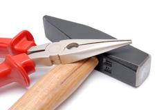 hammer with wooden handle and flat-nose pliers with red handles - stock photo