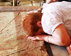 Stock Photo of woman prays at the holy sepulcher - old Jerusalem