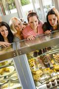 women friends looking at cakes in cafe - stock photo
