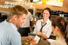 Stock Photo of couple paying bill at cafe cash desk