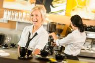 Stock Photo of waitress serving coffee cups making espresso woman