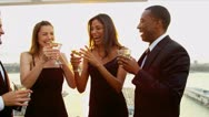 Stock Video Footage of Two women drinking cocktails with men at luxury sunset party dressed in black