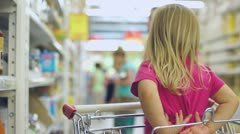 Adorable girl sit in sopping cart in supermarket Stock Footage