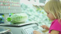 Adorble girl weighting chinese cabbage in supermarket - stock footage