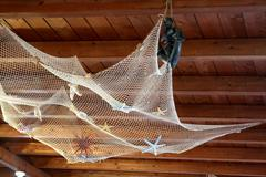 fishing net on wood ceiling - stock photo