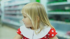 Adorable girl in beautiful dress ride on front side of shopping cart - stock footage