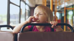 Adorable girl ride bus on passenger seat - stock footage