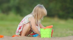 Adorable baby play with small shovel and pail in sand on playground - stock footage