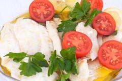 piatto di pesce bianco con pomodorini e prezzemolo - stock photo