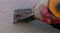 ECU- man chiselling exterior wall Stock Footage