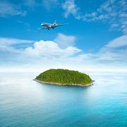 Private jet plane is over a tropical island - stock photo