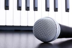 Stock Photo of microphone on piano keyboard background